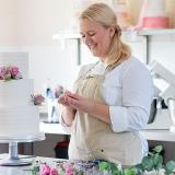 Chef and owner of The Pastry Corner Alexandra Bishop decorating a cake in her shop. Picture by Tash and Will Photography.
