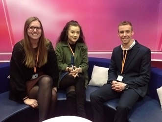 Three journalism apprentices sitting on a sofa in a TV studio