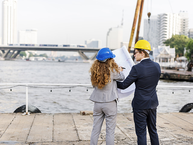 Male and female site planners looking at plan with bridge in the background